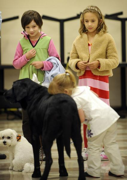 """(tr) CD21SERVICE DOG_CM  9-year-old Allison Winn  (top left)  raised over a $1000 selling dog biscuits to help fund companion dogs to be adopted out  the Denver Women's Correctional Facility on Tuesday October 20, 2009.  Her  7-year-old sister Emily Winn is at top right.   2-year-old Krysta Hubbard, of Riverton, Wyoming who is legally blind,  buries her head in the back of  """"Lucky Bug"""" as she gives him kisses. Winn's dog """"Coco"""" that was also adopted from the prison program sits at lower left.  Cyrus McCrimmon, The Denver Post"""